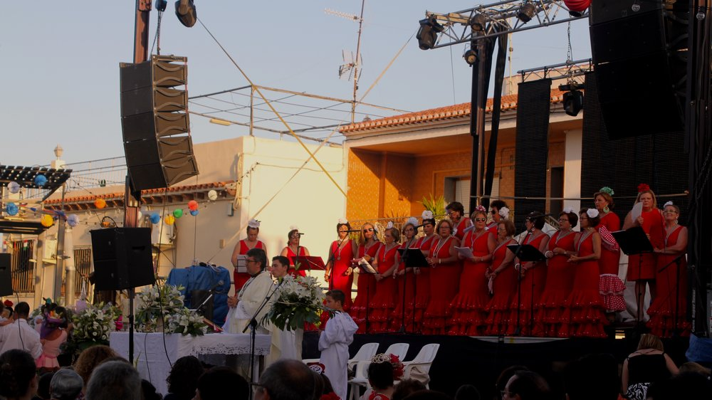 a group of women singing on stage in traditional feria dresses