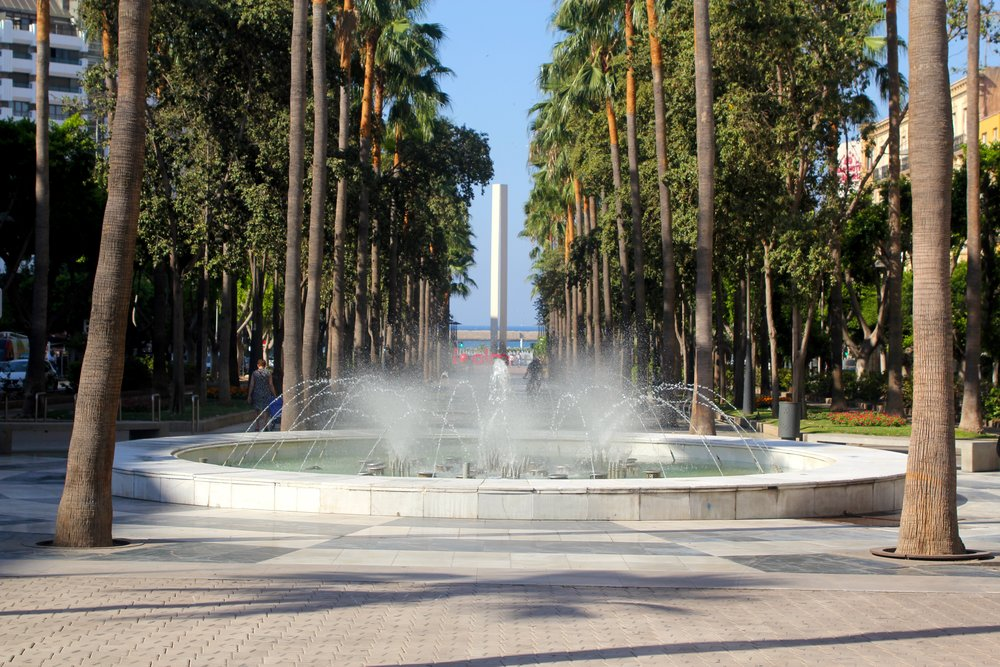 a fountain in the middle of trees lining one of the main roads