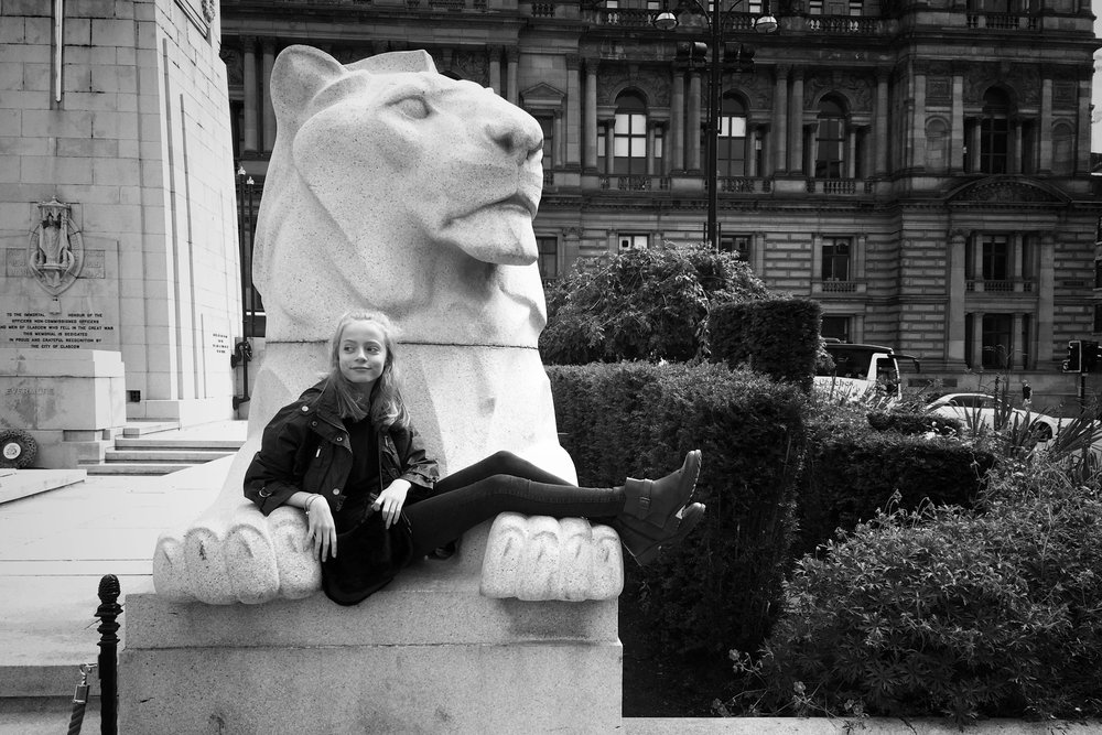 Mia posing with one of the lions in George Square