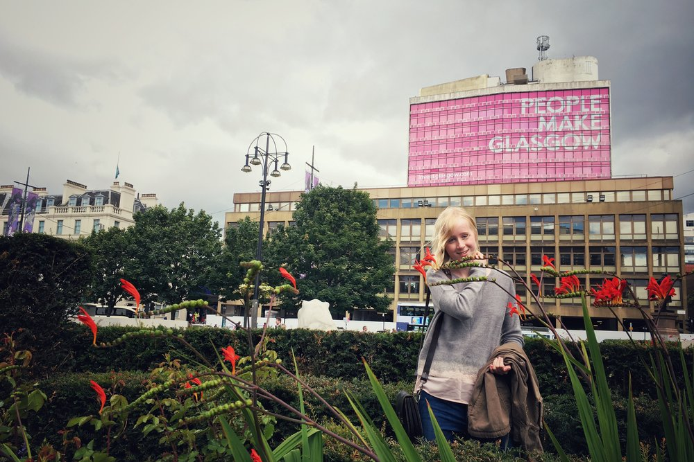 Freja in the gardens at George Square with People Make Glasgow in the background