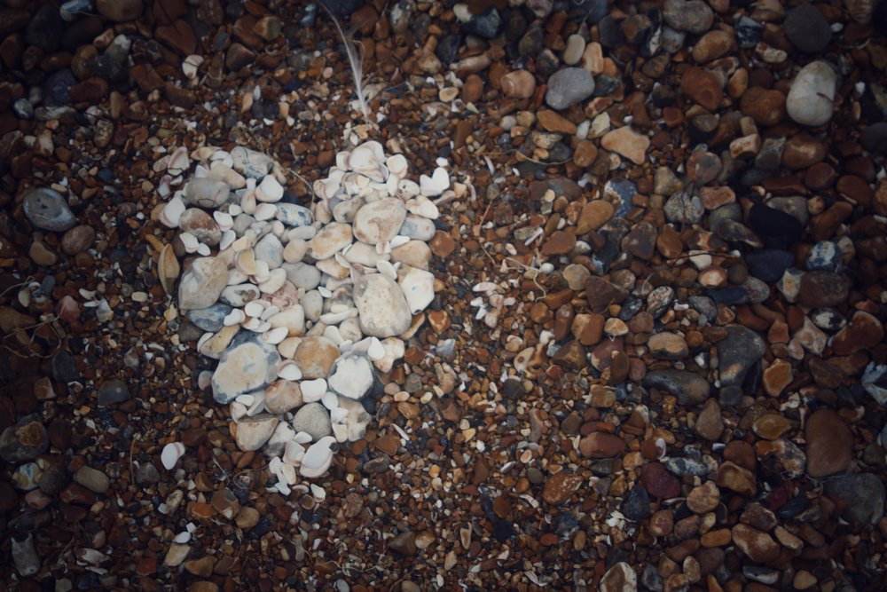 white pebbles arranged in a heart shape on the beach