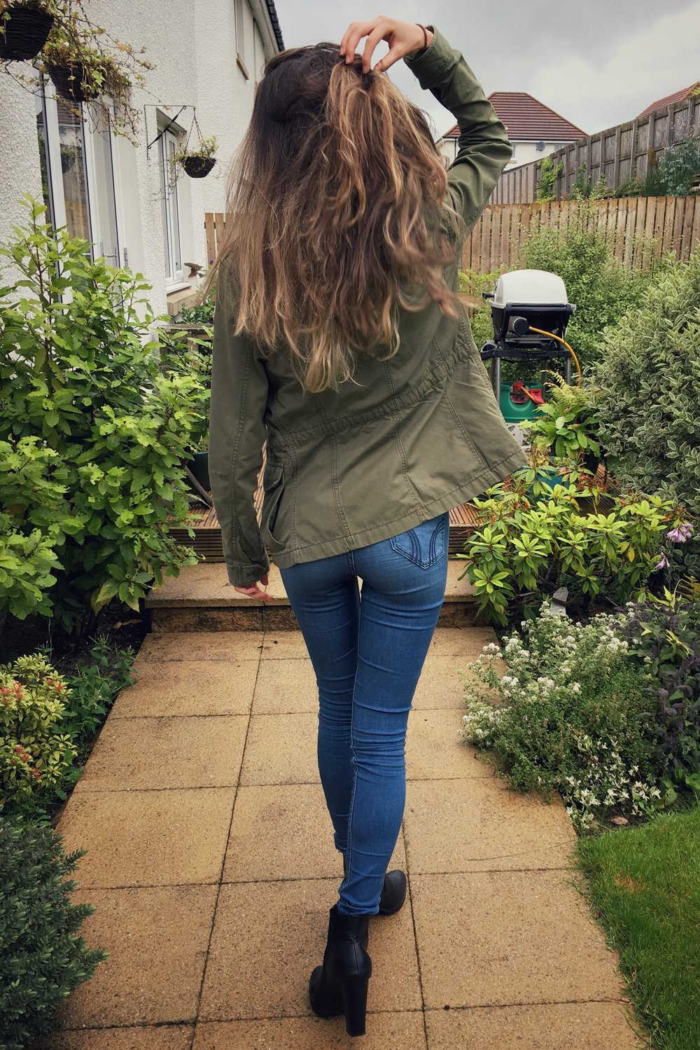 green jacket, denim jeans, grey crop top and black boots