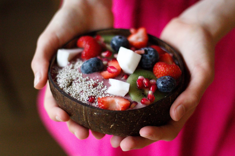 holding a coconut bowl filled with a berry smoothie and toppings