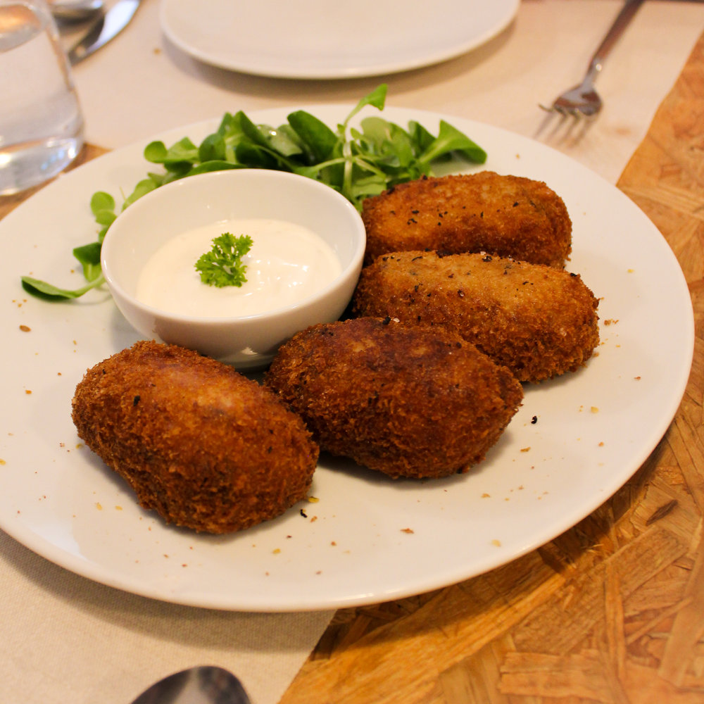sharing plate of croquettes stuffed with mushrooms and smoked vegan cheese, served with aioli