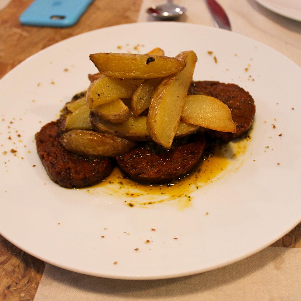 sharing plate of vegan chorizo with chimichurri and potato wedges