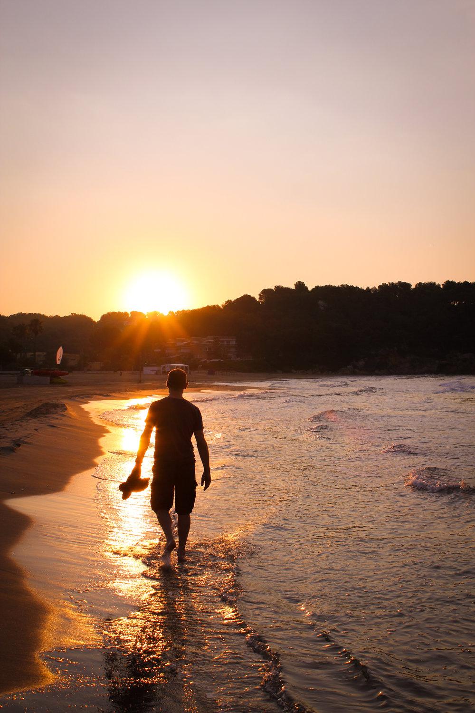 my dad walking along the beach towards sunrise