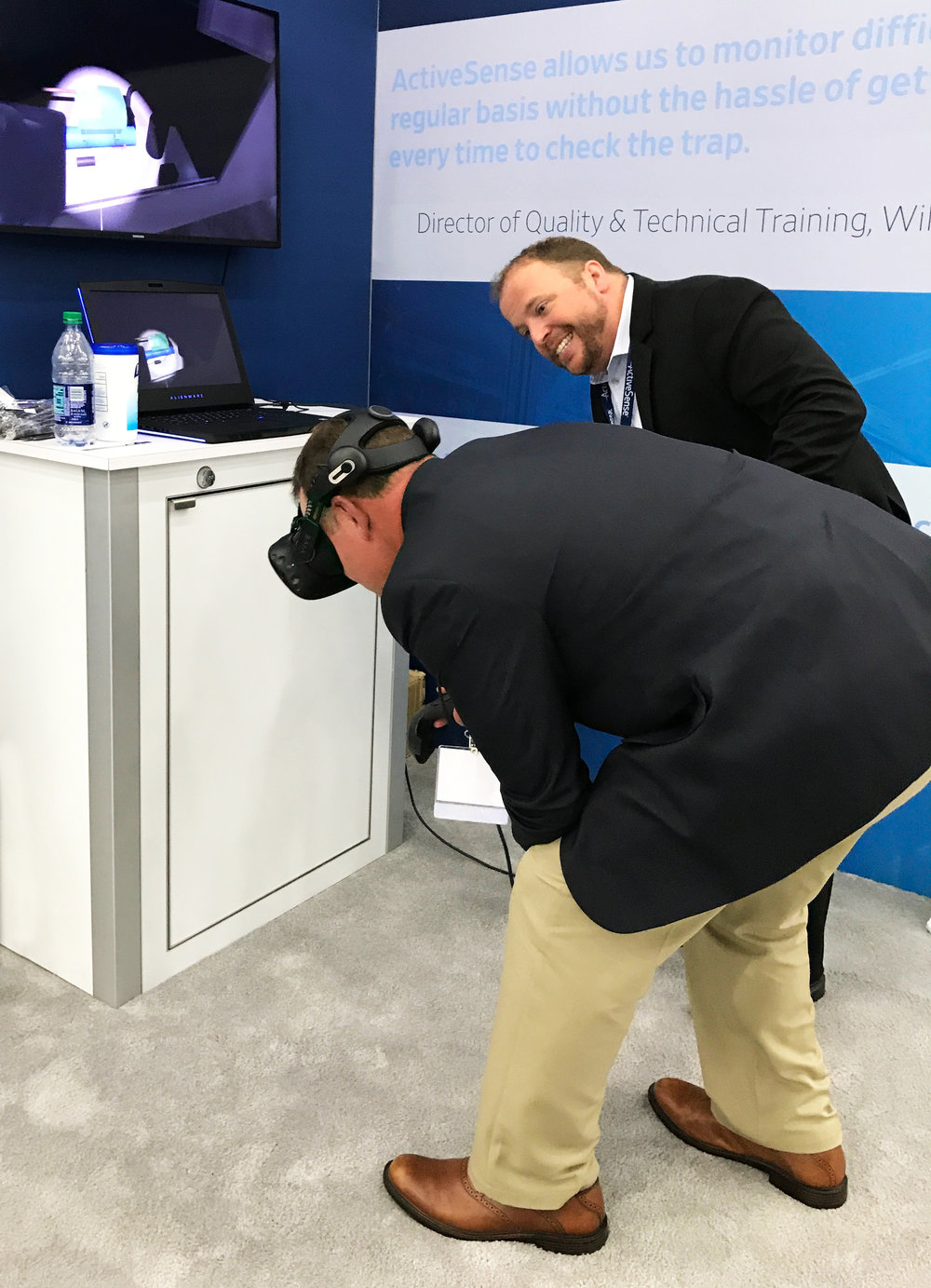 (An attendee of PestWorld 2017 inspects a compressor compartment for evidence of mice infestation with the use of a virtual reality training application built by VisionThree.)