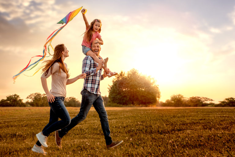 Mother, Father, and young daughter happily flying a kite outdoors.