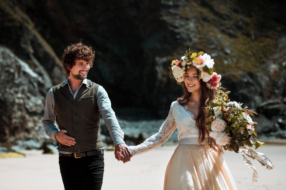 Bride and groom walk hand-in-hand on the beach at their wedding elopement in Cornwall.