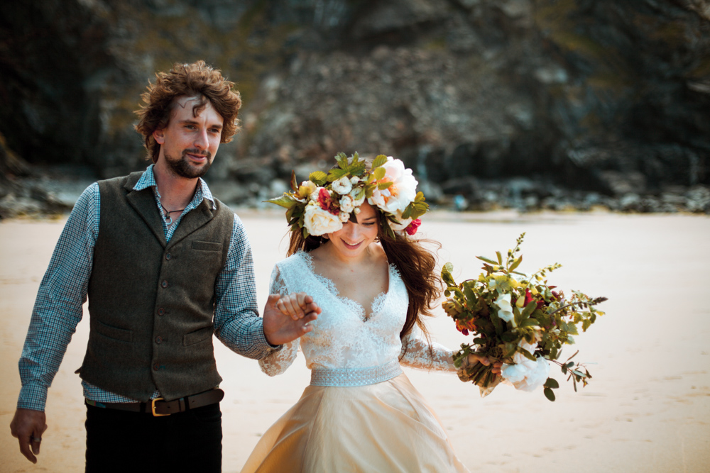 A natural, candid portrait of bride and groom as they walk together on the beach.