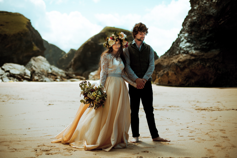 Bride and groom pictured having a moment together on a Cornish beach