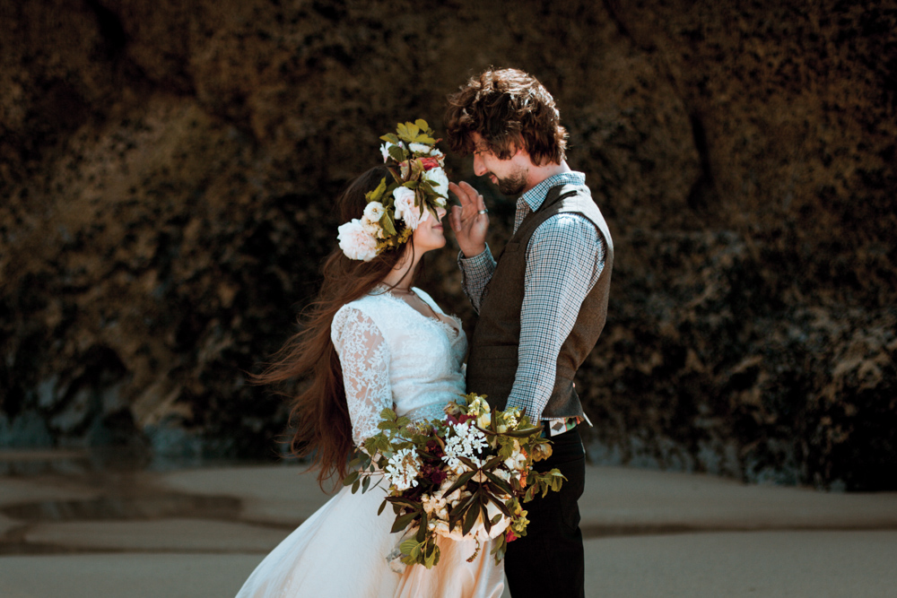 Bride and groom pictured together, with bride wearing a white and peach flower crown.