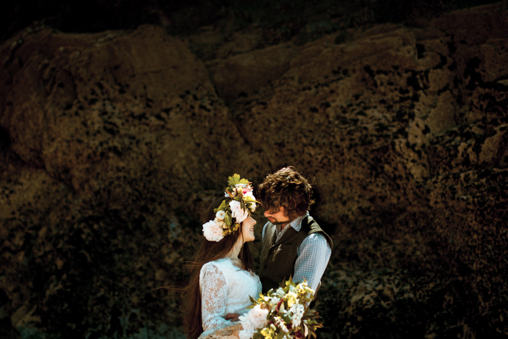 A couple portrait in front of a rocky shoreline after an intimate beach wedding.