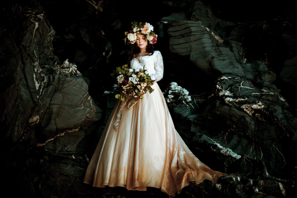 Bride poses on the rocks wearing flower crown and holding bridal bouquet