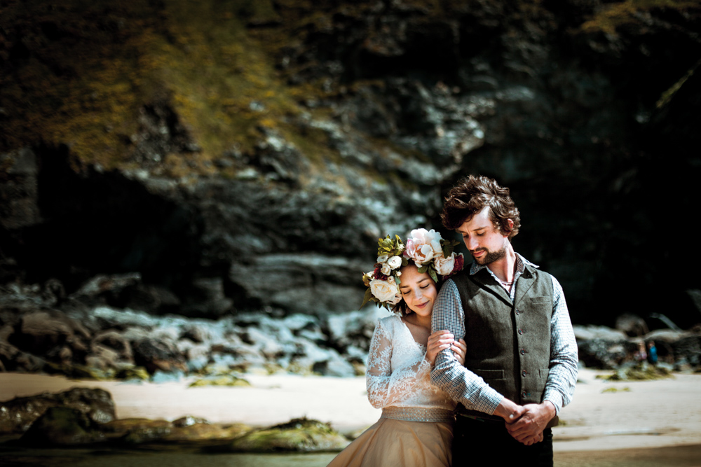 Bride embraces groom on the beach in Cornwall.