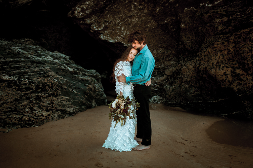 Couple embrace on the beach in front of rocks.