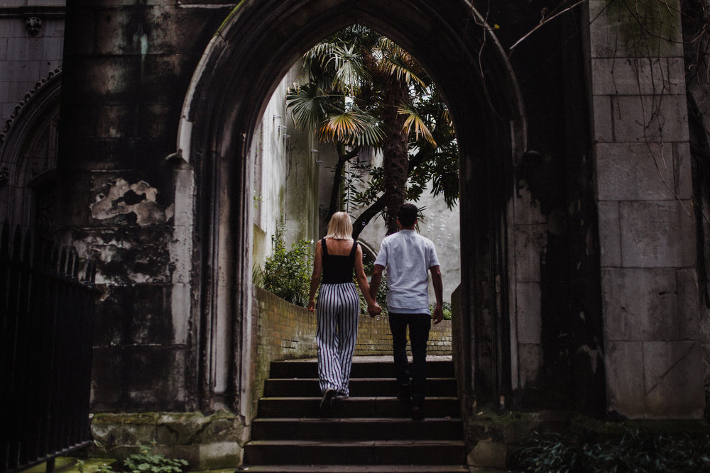 Couple walk hand in hand through the ruins of St Dunstan-in-the-East