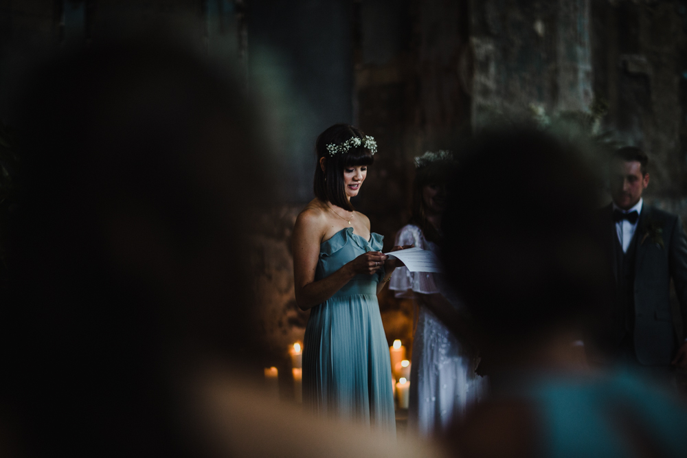 The bridesmaid delivers a reading in candle light during the wedding ceremony.