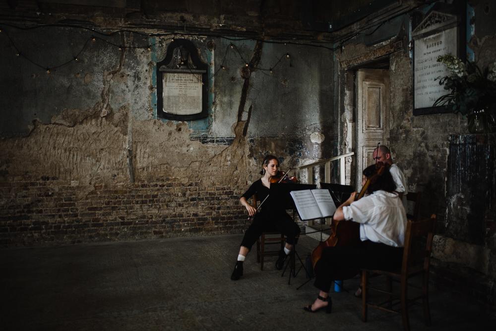 A String trio play as the bride enters for her Asylum Peckham Wedding