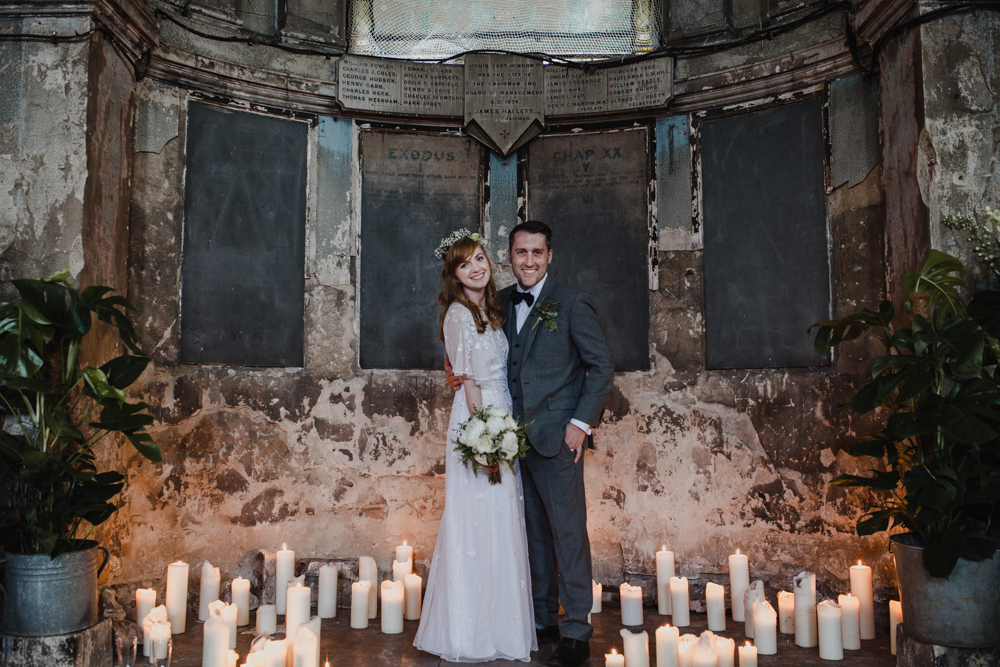 Bride and groom pose for a portrait surrounded by candles in the Asylum Chapel.