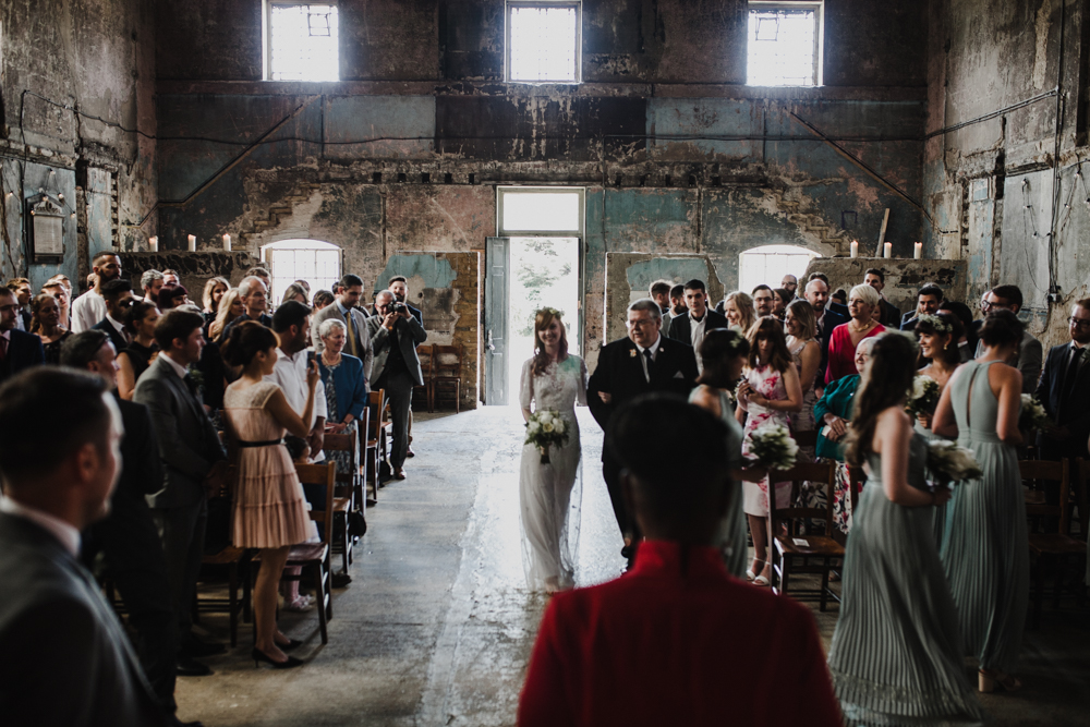 Bride and her dad walk down the aisle to meet the groom at the Asylum Chapel.