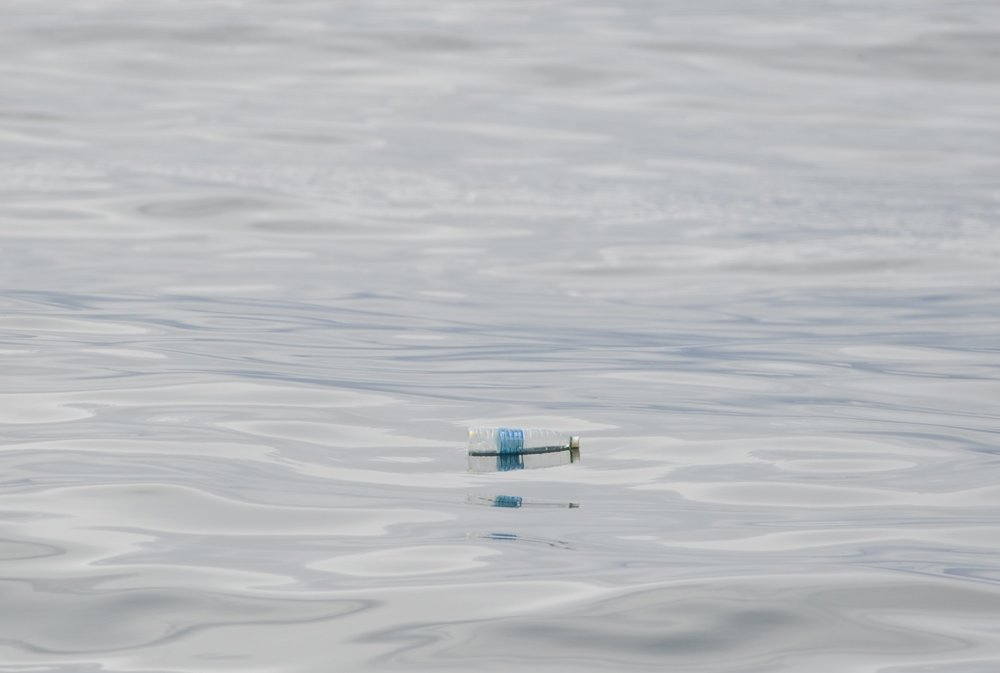 Water bottle floating on a glassy sea. We pick up plastic whenever the sea conditions allow it.