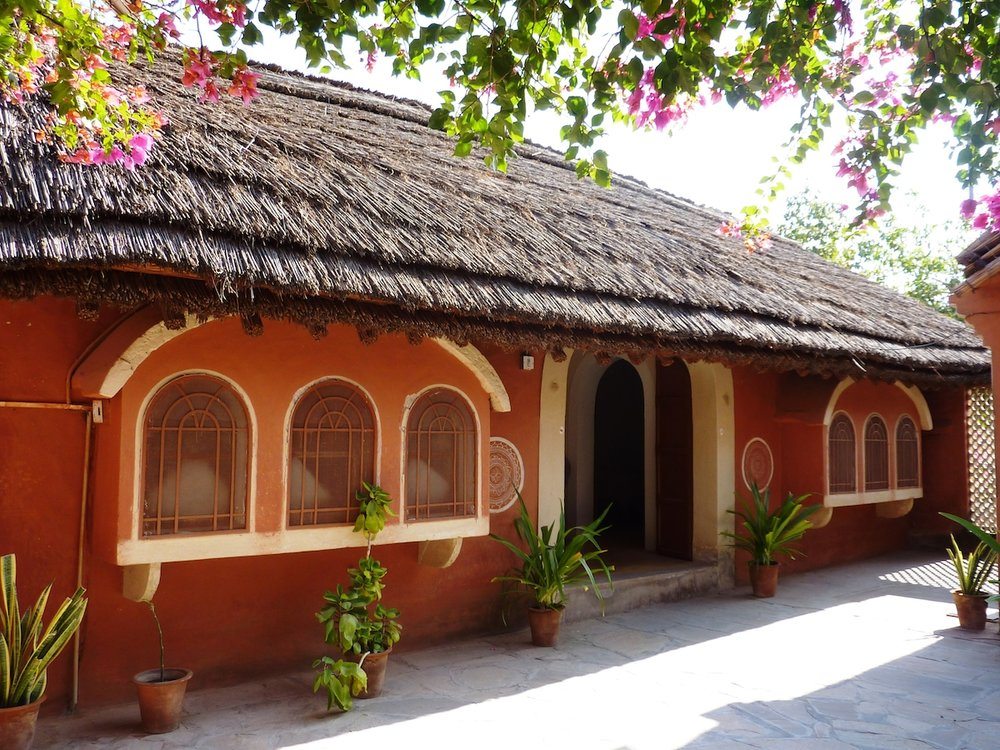 A traditional mud and grass thatched bungalow at Apani Dhani keeps the interior naturally cool in the hot desert climate.