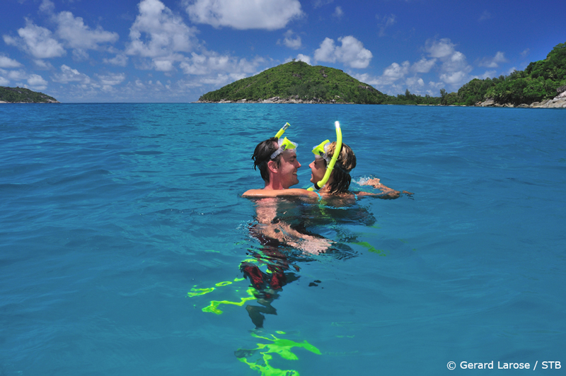 A couple snorkelling at Port Launay; Seychelles is a popular destination for honeymooners.