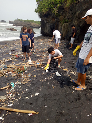 Joe, Josh, Delaney and Pablo from Canggu Community School gathering rubbish. Plastic and naturally degrading driftwood mix together in an unattractive spill on the sand