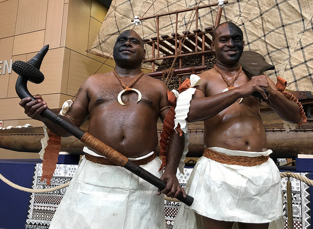Fijians striking a pose in front of the drua display, an ocean Fijian canoe, at the UN Climate Change Conference in Bonn, to symbolise sailing with collective determination for the success of COP23.