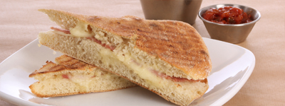 PANINIS  - Served with side salad or nacho chips & salsa*Cheese & Tomato (or onion) made with mild  cheddar*Tuna Melt with mayo & melted Welsh cheddar*Ham & Mozzarella with Cotswolds ham & Italian  Mozzarella*Spicy Chicken with Harissa sauce Chicken & Bacon Club with tomatoes & cheese