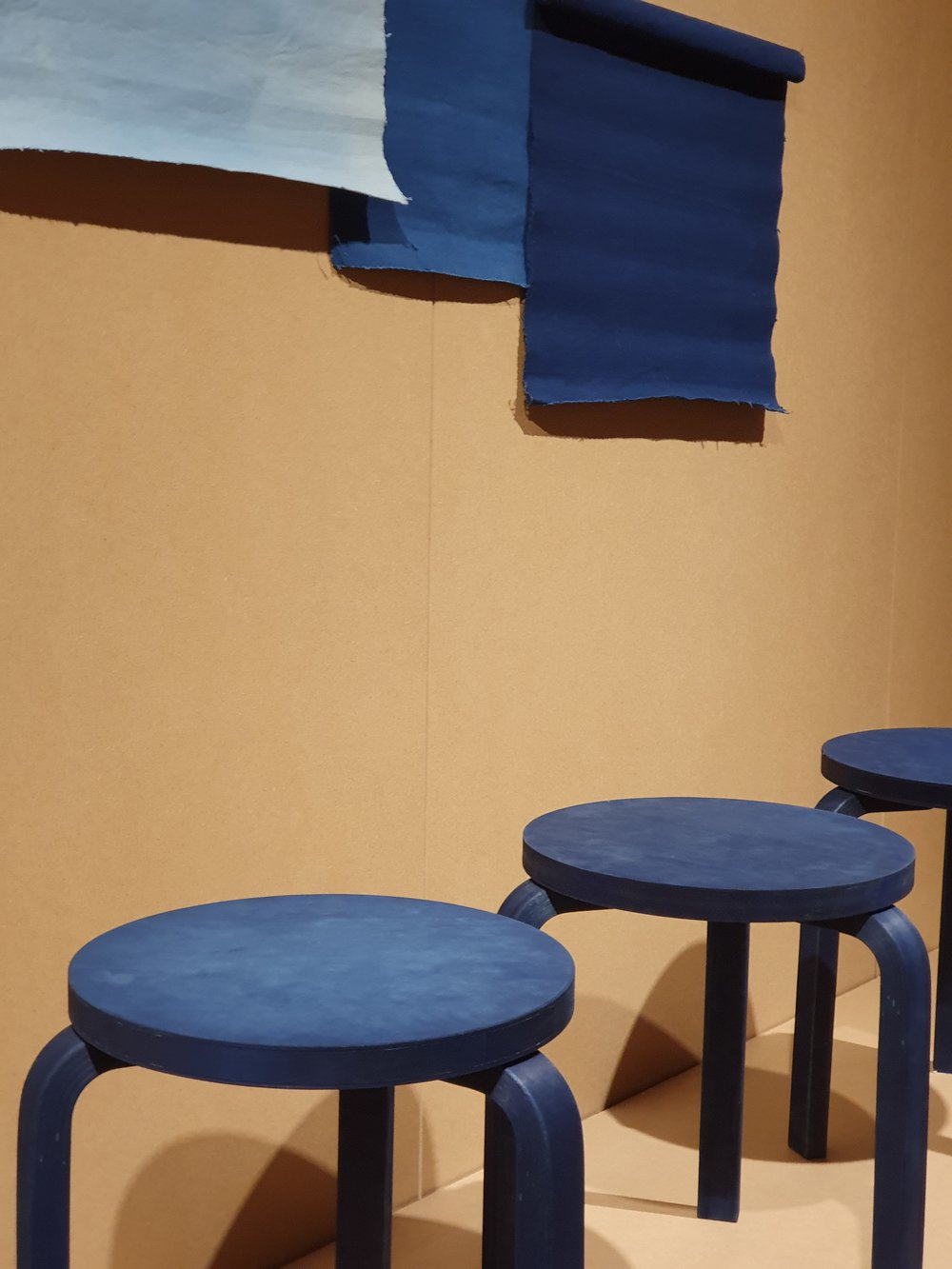 """""""Stool 60 Aizome brings together Alvar Aalto's iconic design with a traditional plant-based Japanese colouring technique. Indigo dyeing, or """"aizome"""" in Japanese, is a popular process used to create denim and is now applied to turn the stool a characteristic deep blue. Often used in fashion and textile design, the tradition of indigo dyeing is deeply rooted in the Japanese conscious and the vibrant colour it produces is also known as """"Japanese blue"""". To create this version of Stool 60, Artek partnered with indigo-dye specialist BUAISOU from the Tokushima prefecture. The indigo they use is among the most difficult dyes to produce, highly prized for its beauty, depth of colour and resistance to running. Employing a technique known as """"Jigoku date"""", which translates as """"producing hell"""", wood lye, bran and shell-ash are mixed, before fermentation. Stool 60 is dipped in this indigo bath, resulting in a strongly pigmented, deep blue surface that still allows the natural grain of the wood to shine through."""