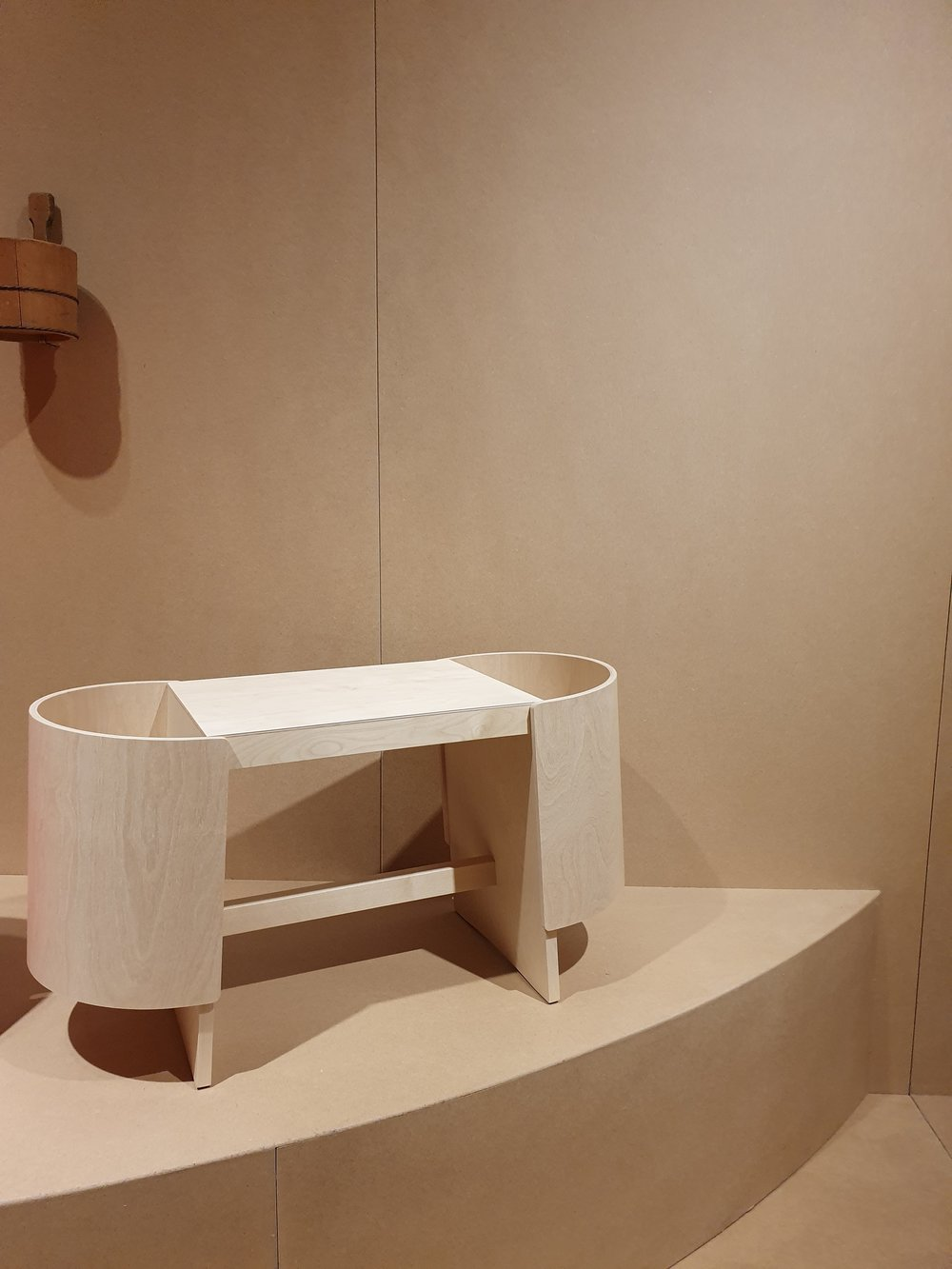 """""""Inspired by the public bathing cultures of both Finland and Japan, Kiulu Bench typifies the refinement and ability to create new archetypes for which designer Koichi Futatsumata is renowned. Public baths, as both social nexus and cleansing ritual, are deeply embedded in the cultural landscapes of both Finland and Japan, and this connection is taken as the designer's starting point. A cylindrically shaped bucket, Kiulu in Finnish, is traditionally used in public baths of both countries and stands at the origin of Futatsumata's bench design. Kiulu Bench serves several functions - as seat and basket, offering storage for items such as towels and cosmetics, magazines or toys. Embodying Futatsumata's concern with material and eye for detail, Kiulu Bench can find its application in the dry surroundings of the bath/spa/wellness area and beyond."""