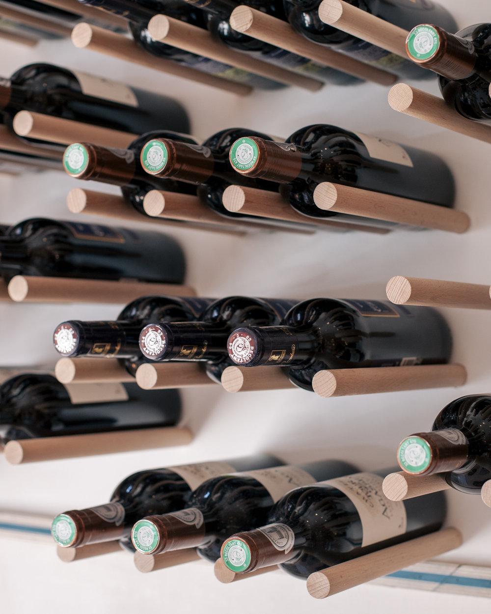 Habillage mural avec un range bouteilles de vin en bois pour le Loyal café