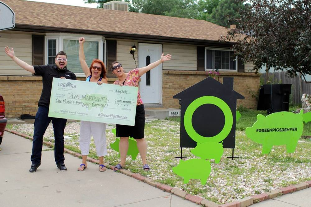 recipients of the green pig foundation mortgage help in front of home with large chek