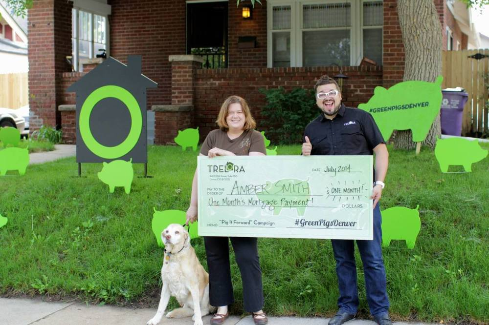 recipient of the green pig foundation mortgage help in front of home with large chek