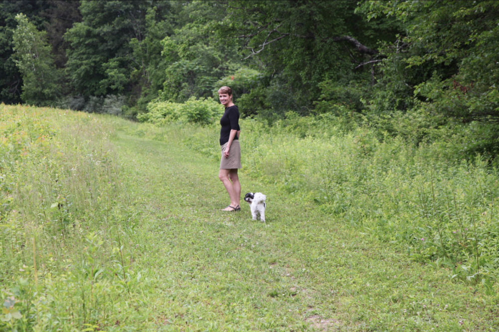 Mary Beth, with her Shih Tzu Bushwick, walks a trail across the lane from her upstate New York home.