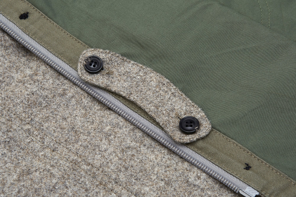 When not needed, tab can be stowed on the inside of placket.