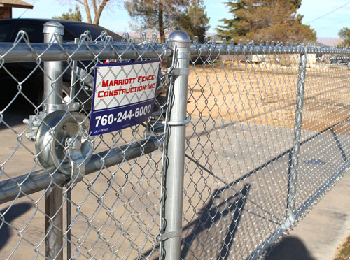 RESIDENTIAL CHAIN LINK - Chain link fencing is one of the most popular choices for residential fences in the High Desert. We can design a fence that suits your needs and budget. Options for a chain link fence include slats to have more privacy and color to your home or business, and heavier posts are used for slats to withstand the winds in the High Desert. Automatic gate openers add convenience to your slide gate. We use American-made products as much as possible.