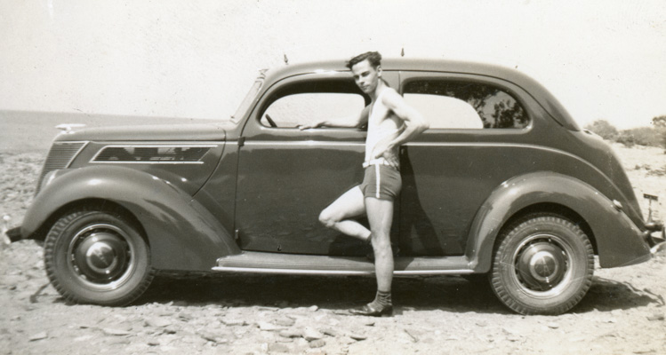 Vintage photograph of man in shorts standing next to antique car