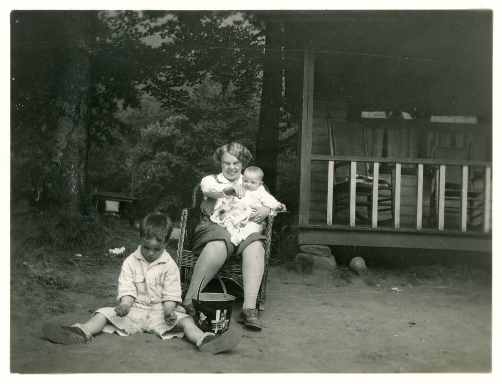 Old photograph of a family on a camping trip in front of an old cabin