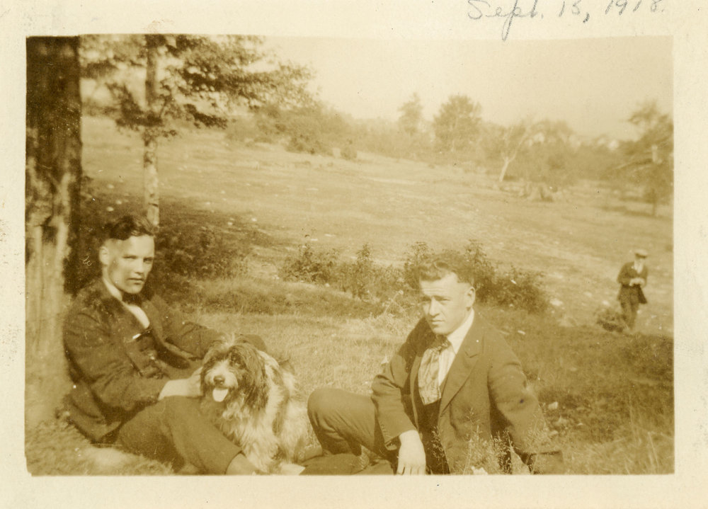 Found photo from 1918 of two men wearing suits with a dog in Maple Grove