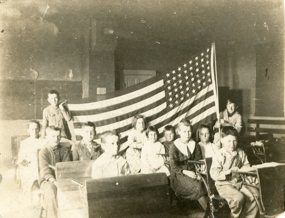 Antique found photography of schoolchildren in old schoolhouse with a 48-star American flag.
