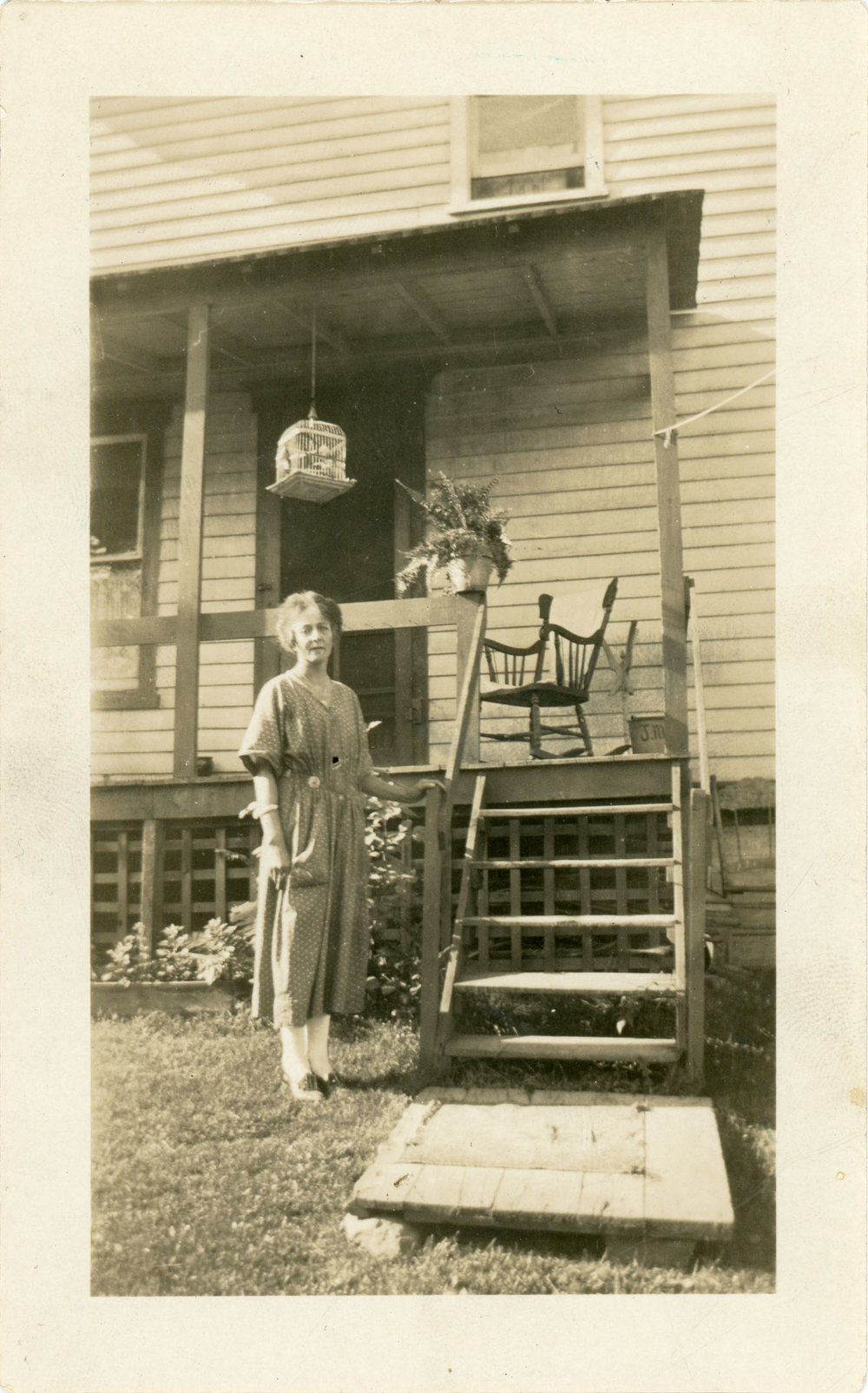 Found photo of woman standing next to a house