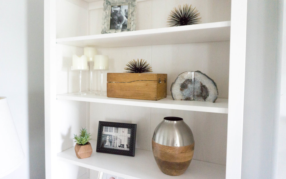 Decorative objects include a mixture of found objects and new. The middle shelf showcases a family recipe box, while the geodes and vase are from Target.