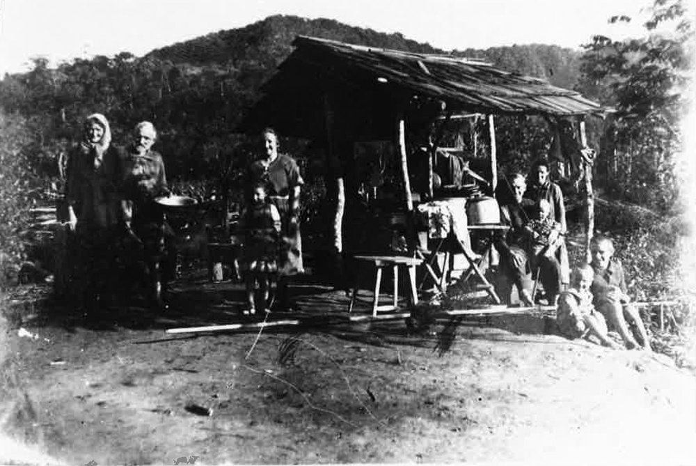 The Neufeld family outside their first permanent home in the Brazilian jungle, where their clock hung.