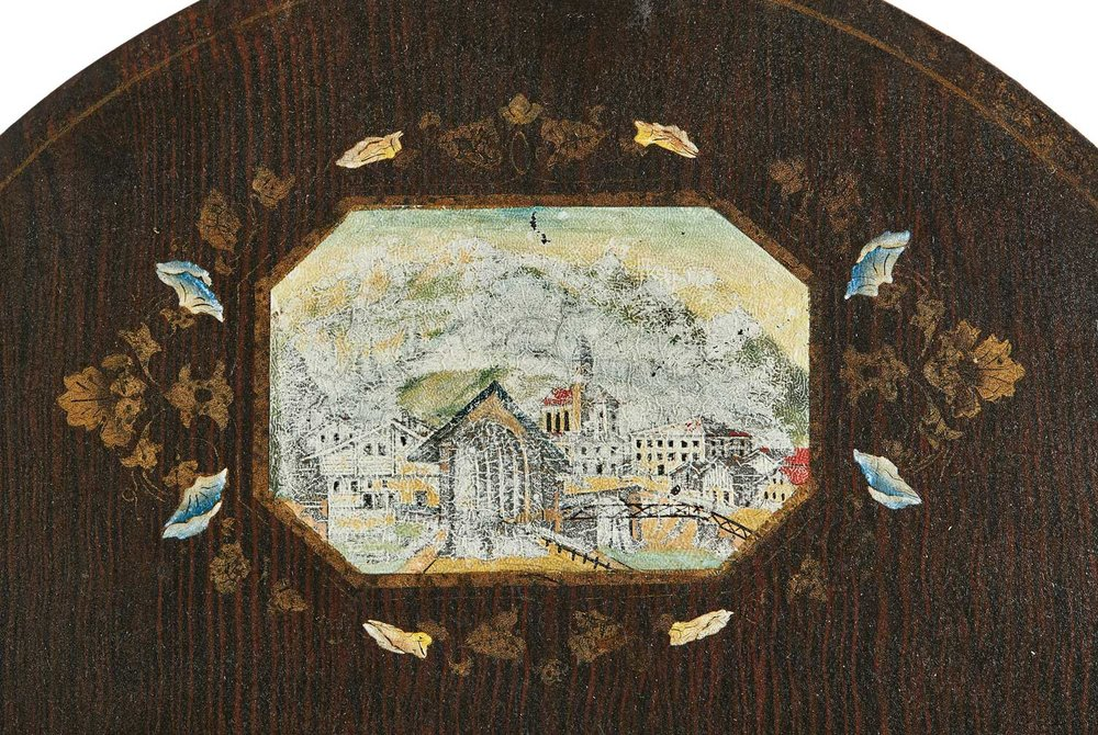 This Mandtler clock face is particularly uusual. It is painted a deep brown and has detailing that appears to imitate a wood grain. While this was a technique sometimes used on traditional Mennonite furniture, it was not commonly used on clocks. It also features a city scene, either real or imagined, in the arch where most Mennonite wall clocks focused on floral or nature scenes.