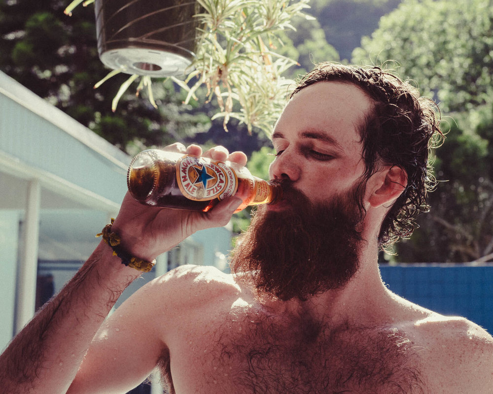 lifestyle photographer Tim Cole shoots man drinking beer by the pool