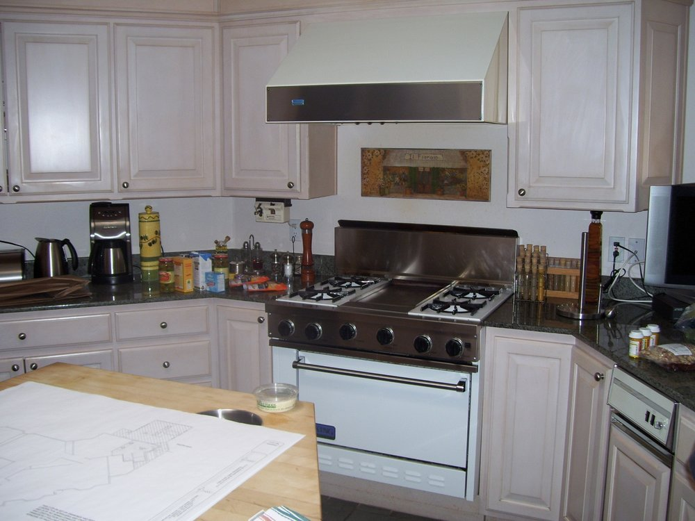 Before- Before kitchen, existing stove with sink to right. Old whitewash cabinets and black corian tops.