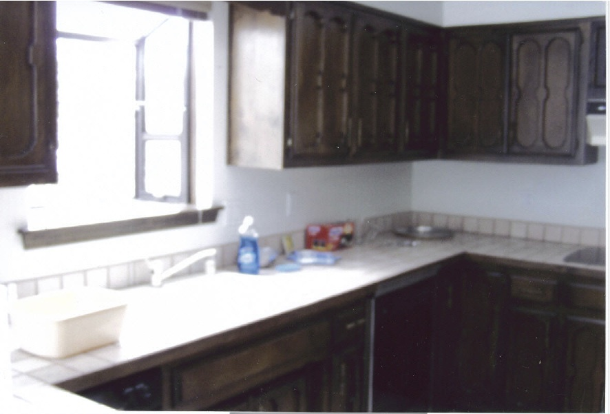Before- Existing kitchen with outdated tile, tops and dark cabinets. Sink and window stayed in same place.